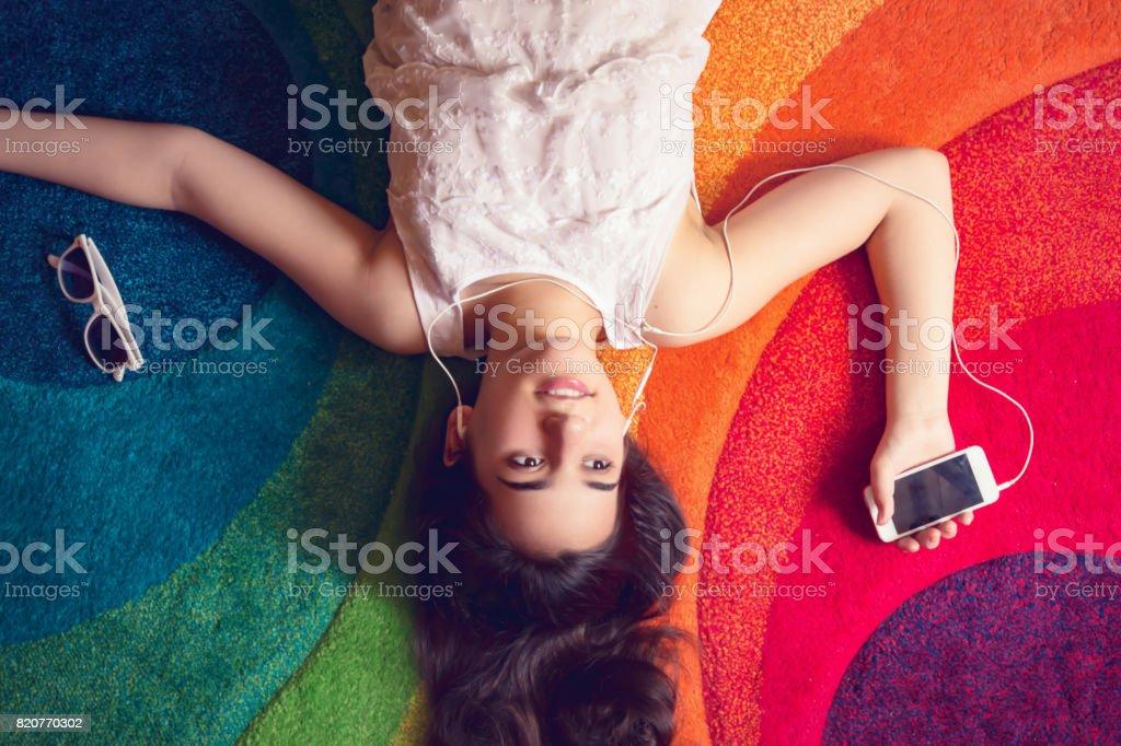 Shiny long hair teenage girl lying upside down on multi-colored...