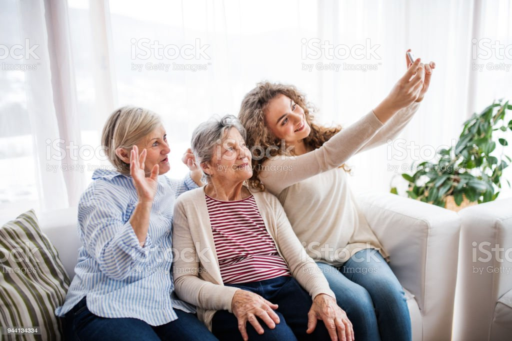 A teenage girl, mother and grandmother with smartphone at home. stock photo