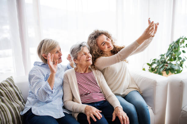 a teenage girl, mother and grandmother with smartphone at home. - three people stock photos and pictures