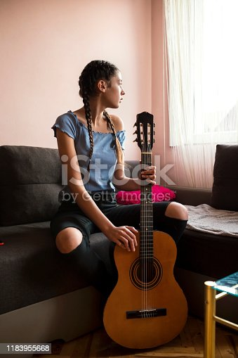 Teenage girl musician composes in her room