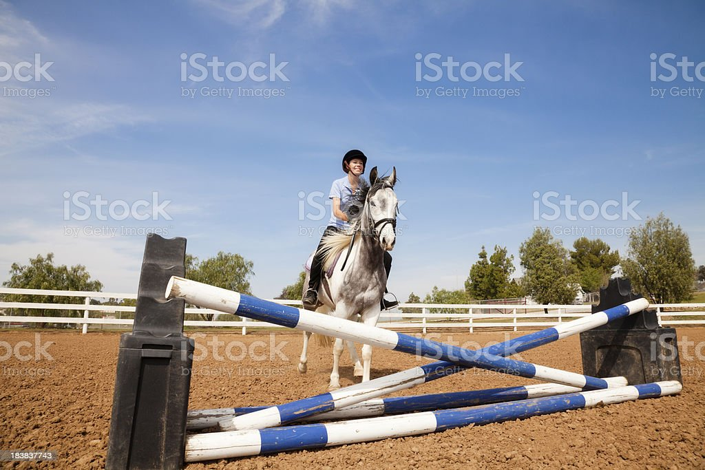 Teenage girl on a horse getting ready to jump royalty-free stock photo