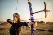 One teenage girl practicing archery outdoors at sunset on the field.