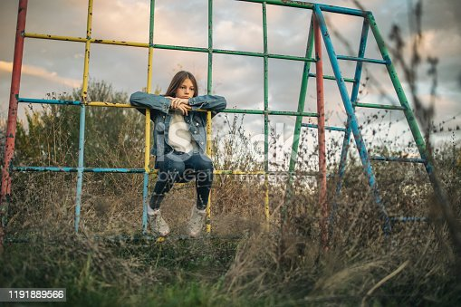 Girl sitting on climbing frame on abandoned playground where she grew up on. Grass is overgrown, playground is rusty and broken. There is no children playing on it anymore.