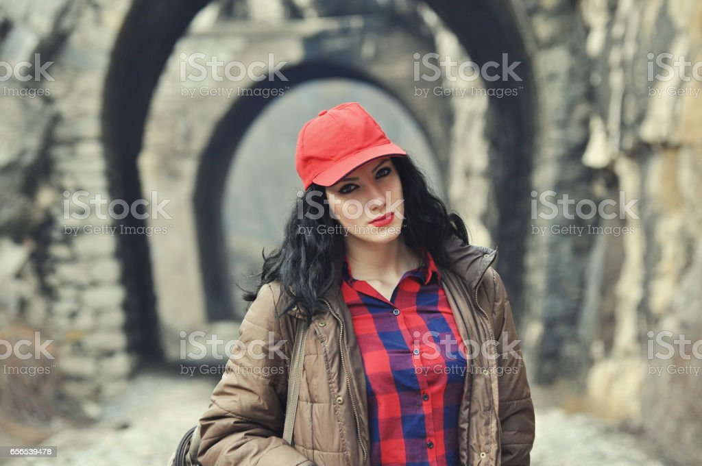 Teenage girl on railway line in front of tunnel. stock photo