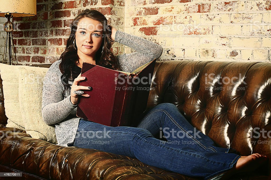 Teenage Girl on Sofa with Book royalty-free stock photo