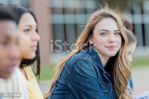 Cute Caucasian teenage girl looks at the camera while waiting for school to start. She is sitting outdoors on campus.