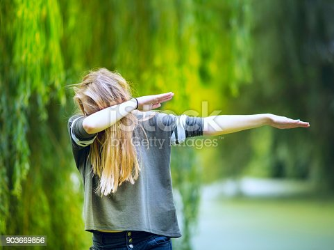 Teenage girl performing a 'DAB'. Dabbing, or the dab, is a simple dance move in which a person drops the head into the bent crook of a slanted arm, often while raising the opposite arm in a parallel direction but out straight.