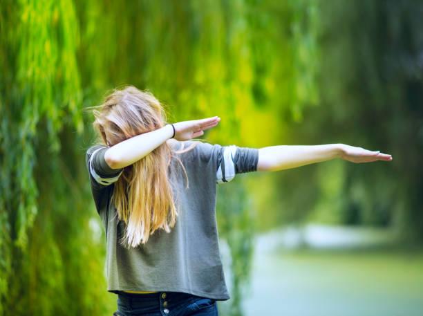 Teenage girl performig a 'DAB'. stock photo