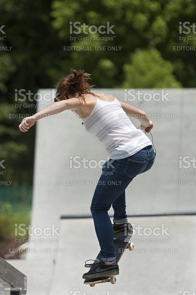 Teenage Girl Performs Jump While Practicing Skateboarding At Park royalty-free stock photo