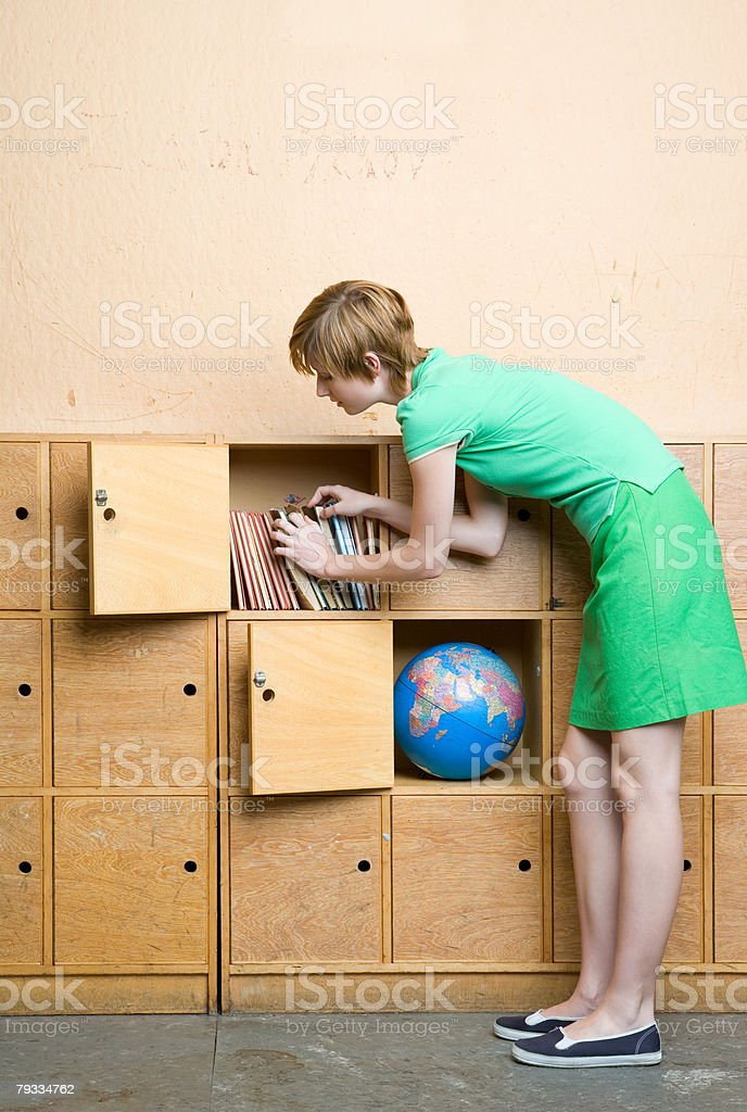 A teenage girl picking books from locker royalty-free 스톡 사진