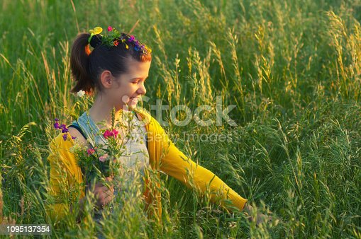 Cute happy teenage girl picking flowers on the meadow on sunny spring day.