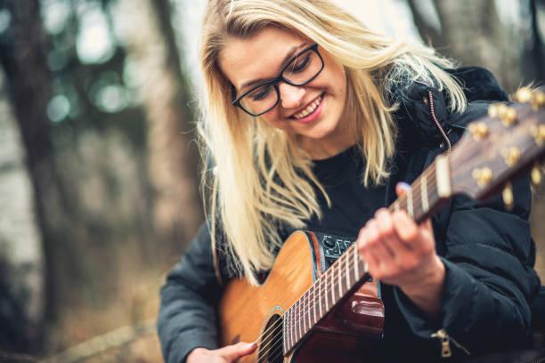 teenager-mädchen spielt akustische gitarre in der natur - one song training stock-fotos und bilder