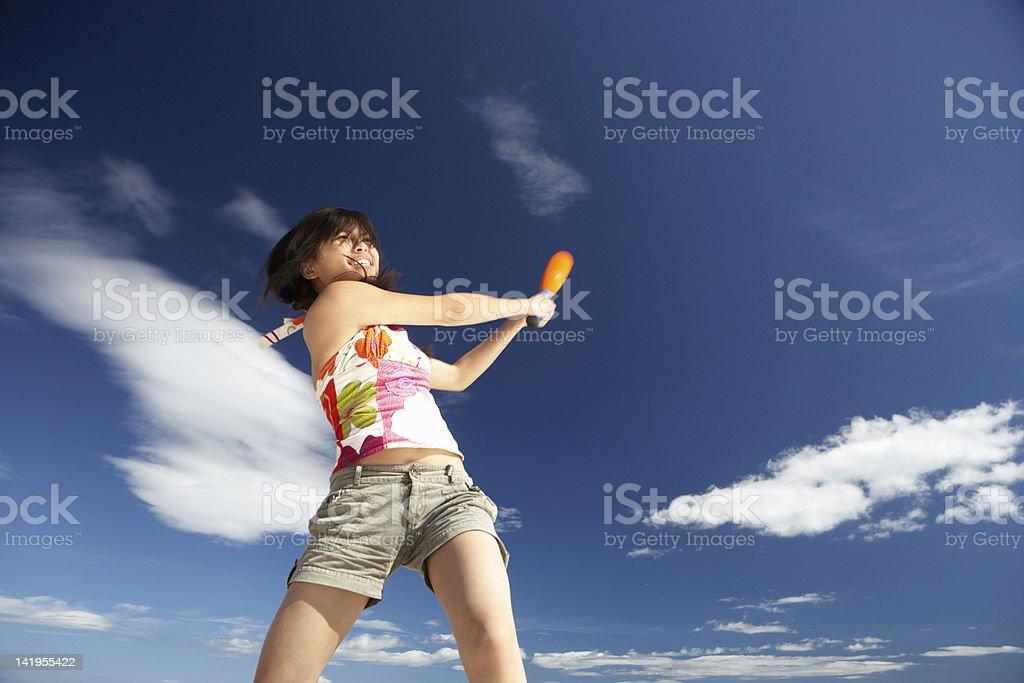 Teenage girl playing baseball on beach stock photo