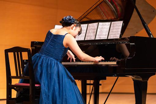 Teenage girl playing piano at concert hall