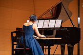 Teenage girl playing piano at concert hall