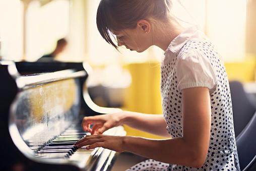 Teenage girl playing piano concert