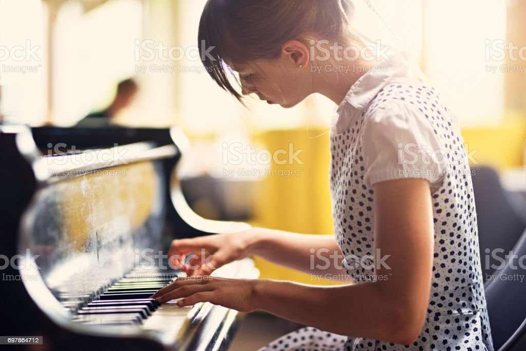 Teenage girl playing piano concert stock photo