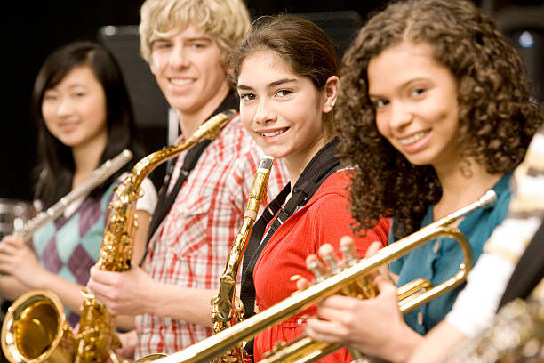 teenage girl playing saxophone in band - performance group stock photos and pictures