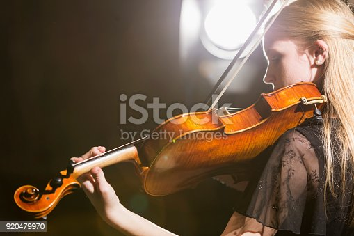 A 16 year old teenage girl playing the violin. She is performing in a black dress. She is looking down at her instrument with a serious expression on her face, concentrating as she plays.