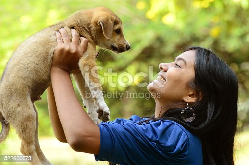 istock Teenage girl playing with puppy dog 522600073