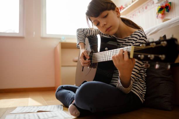 teenager-mädchen üben gitarre - one song training stock-fotos und bilder