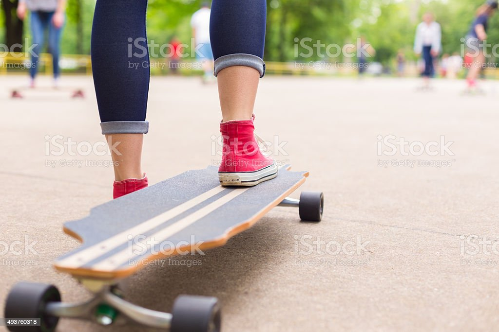 Teenage girl practicing riding long board. stock photo