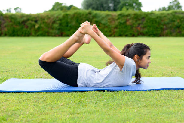 Teenage girl practising yoga outdoors stock photo