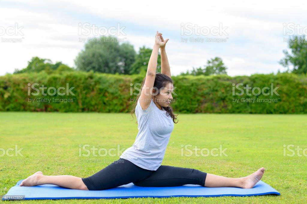 Teenage girl practising yoga outdoors stock photo