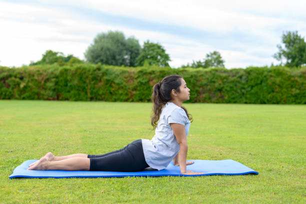 Teenage girl practising yoga outdoors Portrait of teenage girl practising yoga on mat outdoors, Cobra Position cobra pose stock pictures, royalty-free photos & images