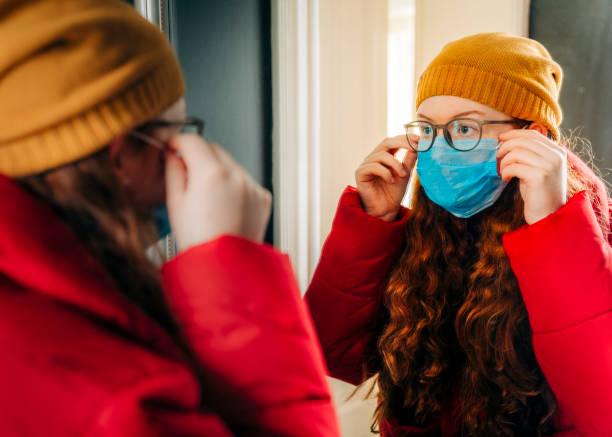 tiener die voor school voorbereidingen treft die beschermend masker dragen - mirror mask stockfoto's en -beelden