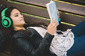 istock Teenage girl reading a book and listening to the music 498759344