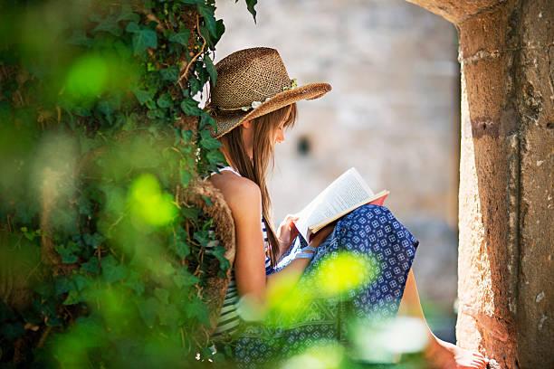 teenage girl reading a book in old garden. - der geheime garten stock-fotos und bilder