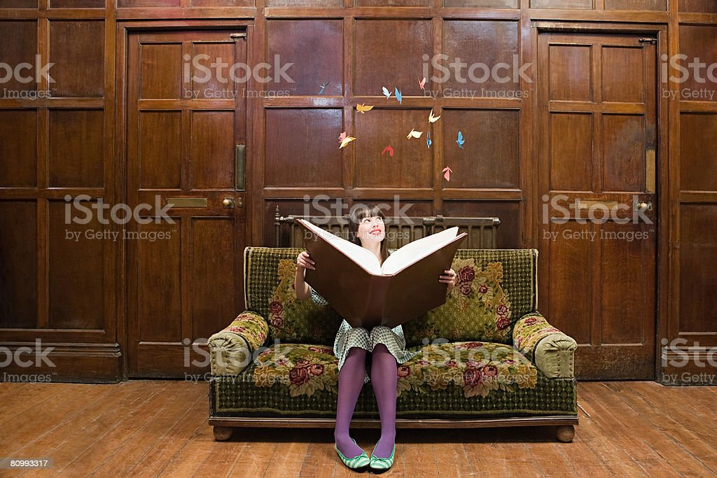 A teenage girl reading a large book stock photo