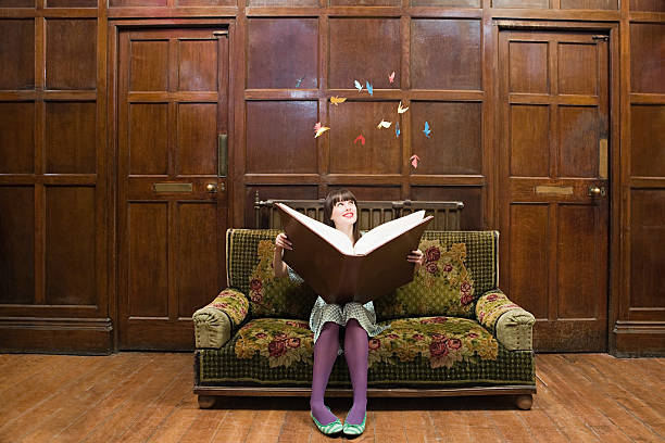 a teenage girl reading a large book - dreamlike stock photos and pictures