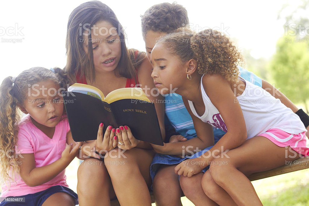 Teenage Girl Reading Bible To Siblings At Park stock photo