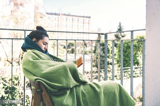 teenage girl wrapped in green blanket reading book on balcony