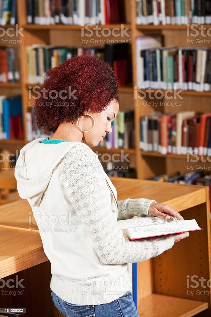 Teenage girl reading in library stock photo
