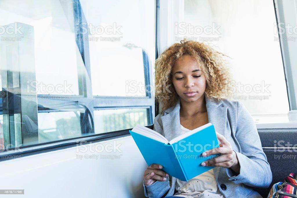 Teenage girl reading on tram stock photo
