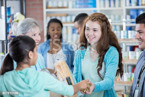 istock Teenage girl receives a donation from food bank 827810156