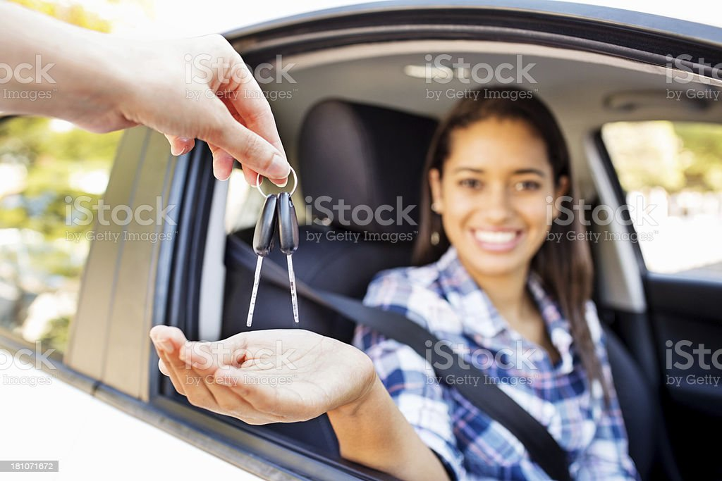 Teenage Girl Receiving Keys While Sitting In Car stock photo