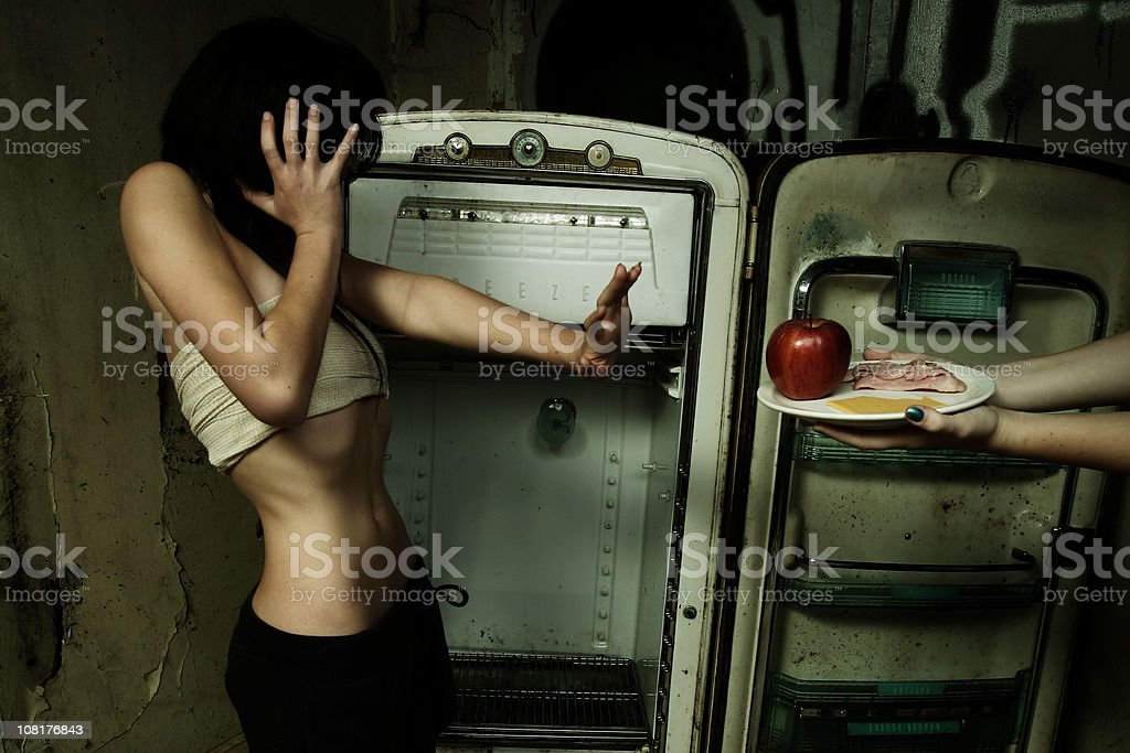 Teenage Girl Refusing to Eat Food in Grungy Kitchen stock photo
