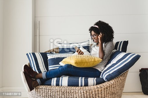 Teenage girl resting listening to music on her mobile on the living room sofa