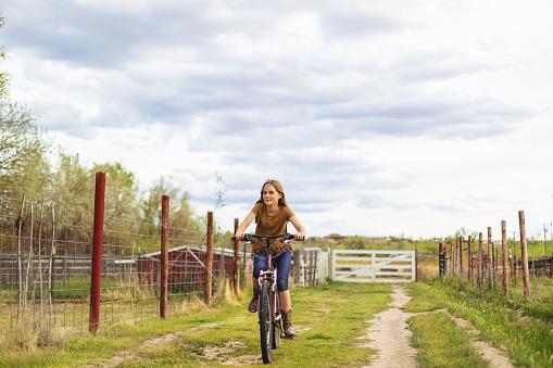 Teenage Girl Riding Bike on the Farm in Western USA