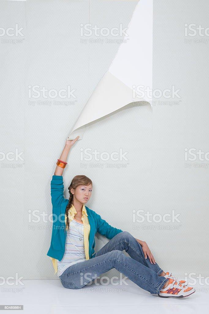 A teenage girl ripping wallpaper 免版稅 stock photo