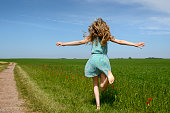 Teenage girl running on a green meadow with poppies under blue sky in springtime. The barefoot girl has long blond hair and she is wearing a light blue sundress. Her arms are outstretched. The girl has a northern european descent. Taken with copy space from rear view. Horizon over land in the background.