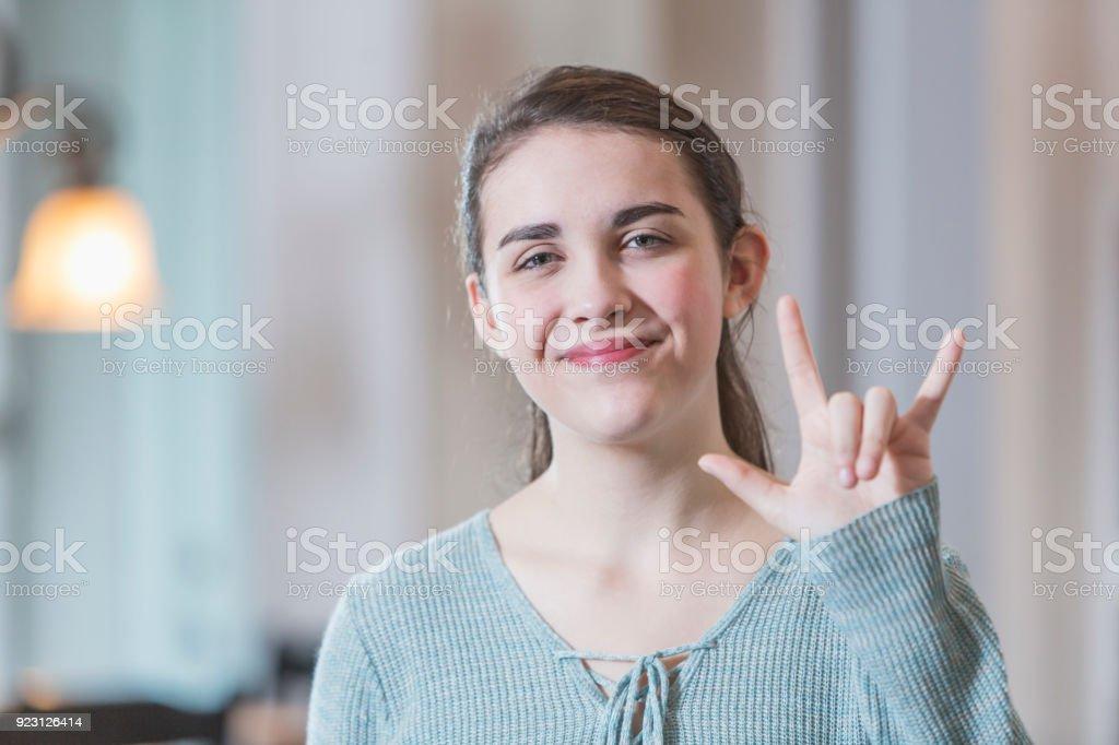Teenage girl saying I Love You in sign language stock photo