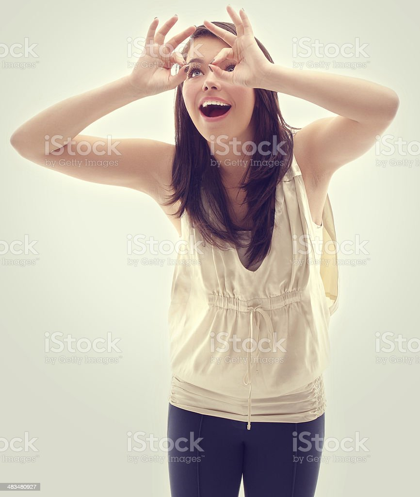 Teenage girl shielding eyes and looking on stock photo