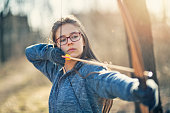 Teenage girl drawing a bow outdoors on winter day.\nNikon D850.