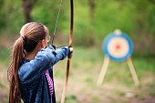 istock Teenage girl shooting bow at target in the forest 1223276834