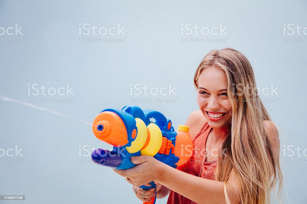 Teenage Girl Shooting Squirt Guns stock photo